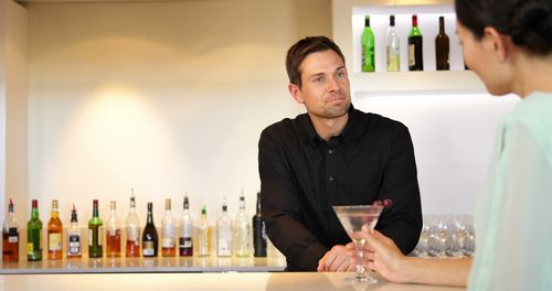 Stock-footage-bartender-serving-a-cocktail-and-chatting-to-customer-at-the-local-bar
